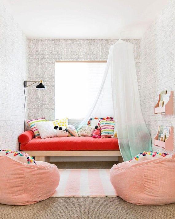 kleine kinderzimmer modern und hell gestalten durch spielerisch gemusterte wandtapete, tagesbett mit baldachin vor dem fenster,puff-kissen in hellrosa und kleine holzbücherregalen