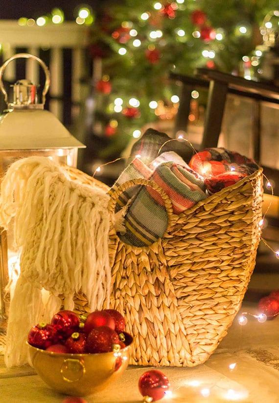 veranda weihnachtlich und gemütlich dekorieren mit lichterketten, roten chritsbaumkugeln in goldschale und winterdecken in weidenkorb
