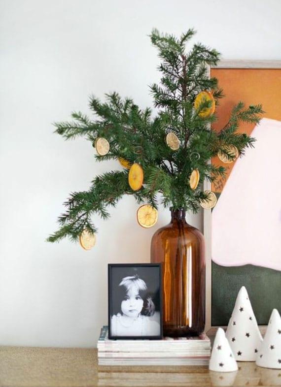 tisch und sideboard weihnachtlich dekorieren mit tannenzweigen und orangenbaumschmuck in glasvase braun