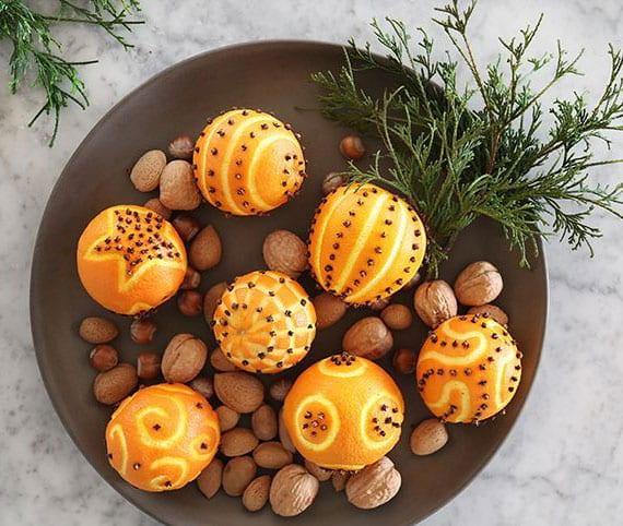 attraktive tischdeko zu weihnachten mit ganzen orangen,nüssen und immergrünzweig in keramikschale braun
