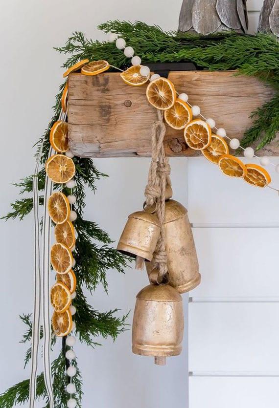 kamin weihnachtlich dekorieren mit glocken, orangenscheiben und diy tannengrün-girlande und