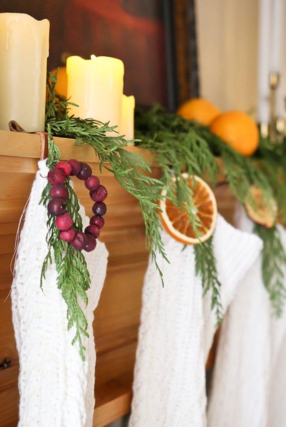 natürliche und rustikale weihnachtsdeko selber machen mit kerzen, immergrünzweigen, orangen und weißen nikolausstrümpfen