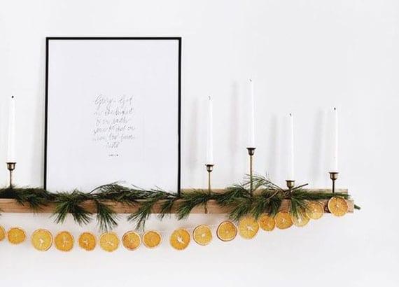 holzwandregale modern und weihnachtlich dekoriren mit girlande aus tannenzweigen und orangenscheiben, weißen kerzen in metallkerzenhaltern und bild in schwarzem bilderrahmen