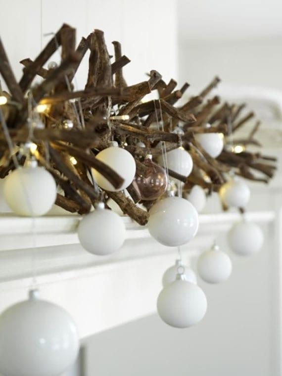 puristische und elegante kamin weinachtsdeko mit diy girlande aus getrockneten zweigen, weißen christbaumkugeln und lichterkette