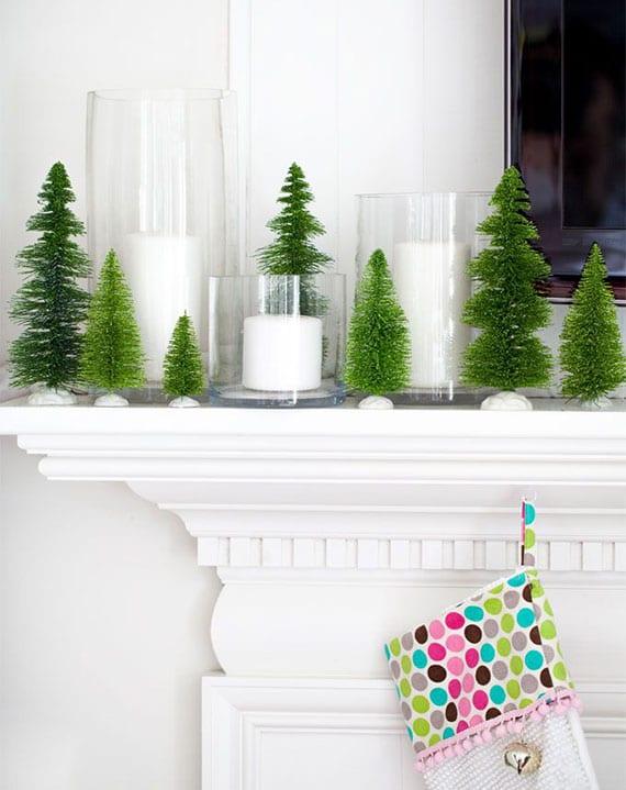kamin im winter festlich dekorieren mit weißen kerzen in glasbehältern und kleinen diy tannenbäumen aus flaschenbürsten