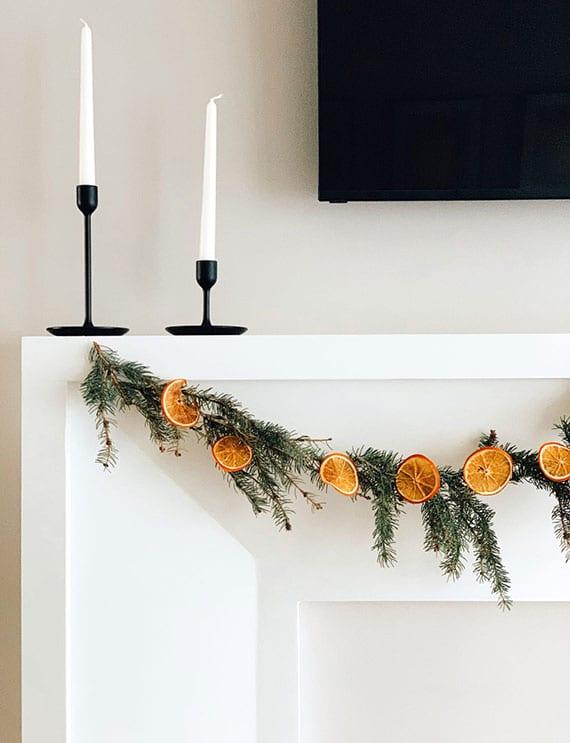 einfache und moderne winterdeko am kamin mit schwarzen kerzenhalter, tannenzweigen und getrockneten orangen