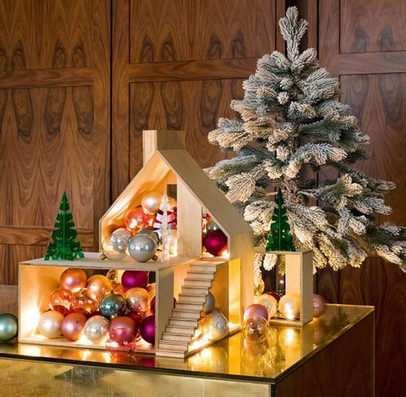 kreative weihnachtsdeko idee mit gruppen von bunten christbaumkugeln in metallischen look und lichterkette in einem holzhausmodell