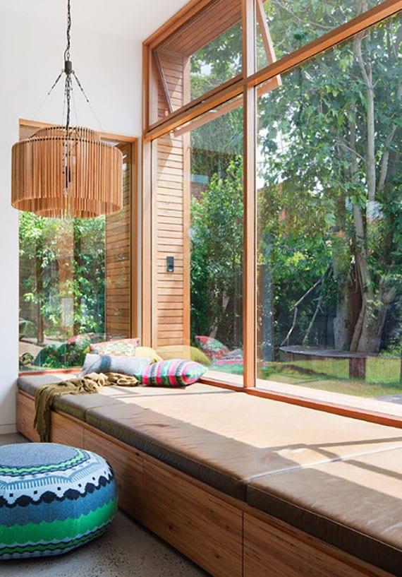 kreative schlafzimmergestaltung mit großformatigen holzfenstern und breiter sitzbank mit schubladen und lederpolstern