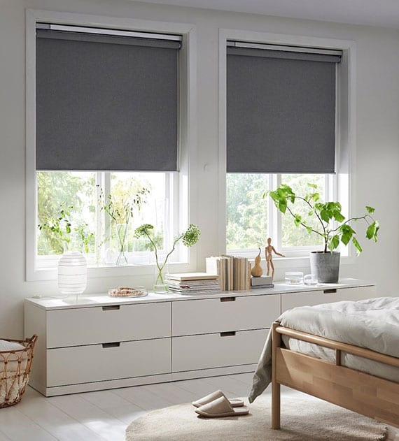 schlafimmer elegant und praktisch einrichten mit niedriger kommode in weiß unter dem fenster, grauen fensterrollos und teppich auf weißem holzboden