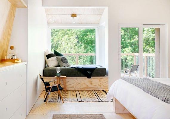 kleines schlafzimmer modern und gemütlich einrichten mit kleiner leseecke mit rundem holzbeistelltisch vor panoramafenster, wandnische mit weißer kommode gegenüber holzbett