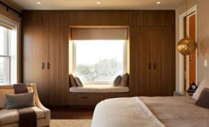 schlaue schlafzimmereinrichtung mit holzkleiderschrank um fensterplatz mit sitzfläche und stauraum