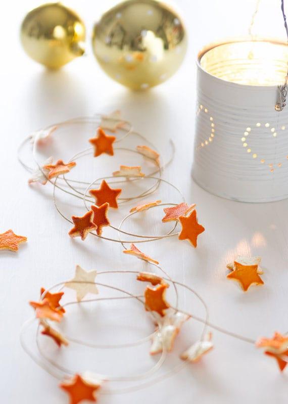 moderne winterdeko mit goldenen christbaumkugeln, diy laterne aus dose und sternen aus orangenschale