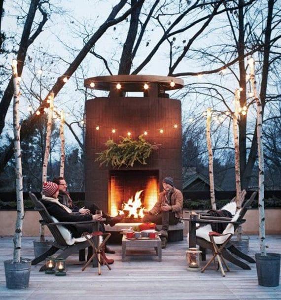 winterparty auf der terrasse vor dem außenkamin_coole terrassengestaltung mit lichterkette auf birkenholz-stützen