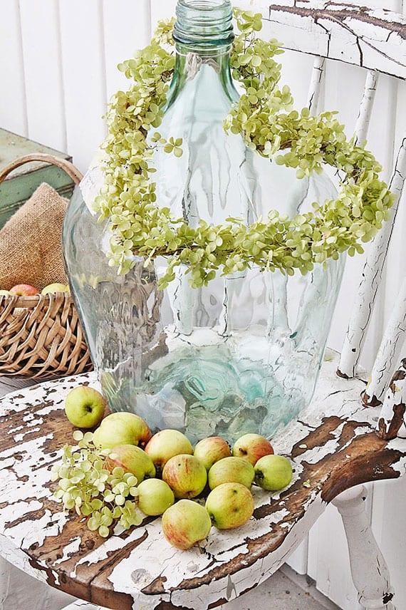 rustikale deko selber machen mit diy Hortensie-Kranz in Herzform, Glasballon und grünen äpfeln uaf einem holzstuhl