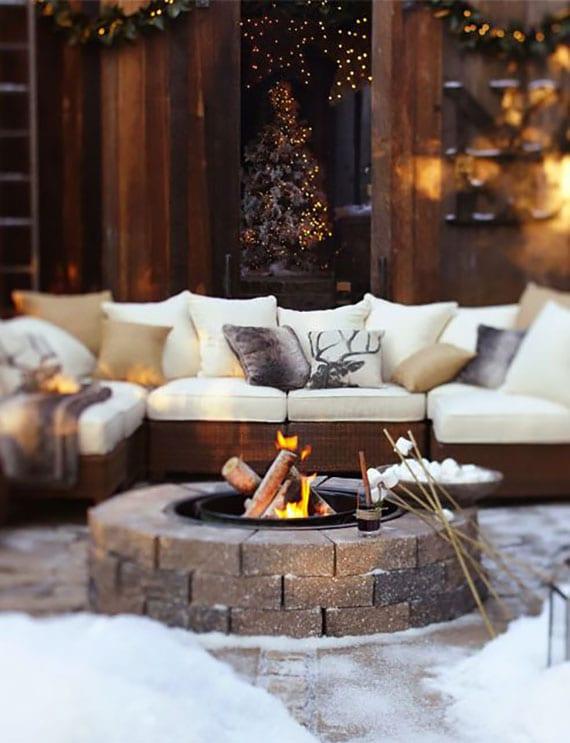 garten im winter gemütlich einrichten mit rattansofa und vielen kissen vor offener feuerstelle
