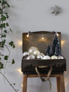 interessante-deko-mit-weihnachtskugeln-und-mini-tannenbäumen-in-einem-koffer