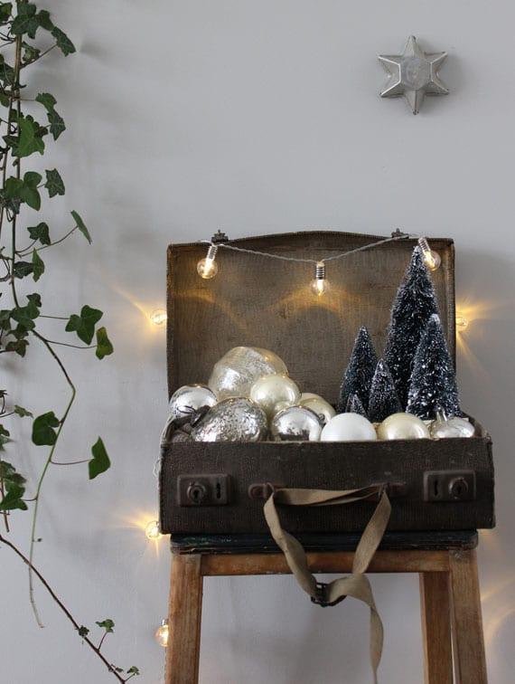 diy weihnachtsdeko mit gluhbirne-lichterkette, dekorativen tannenbäumchen und christbaumkugeln in gold und silber in einem vintage koffer