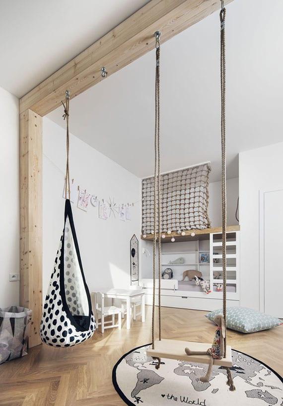 skandinavische kinderzimmer gestaltung in weiß und holz mit spielbett in wandnische mit leiter und seilnetz, holzschaukel und hängehöhle, kindermöbel weiß, rundem teppich auf parkettboden