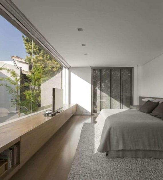 modernes schlafzimmer mit boxspringbett auf grauem teppich, panoramafenster und holz-bank als TV-regal