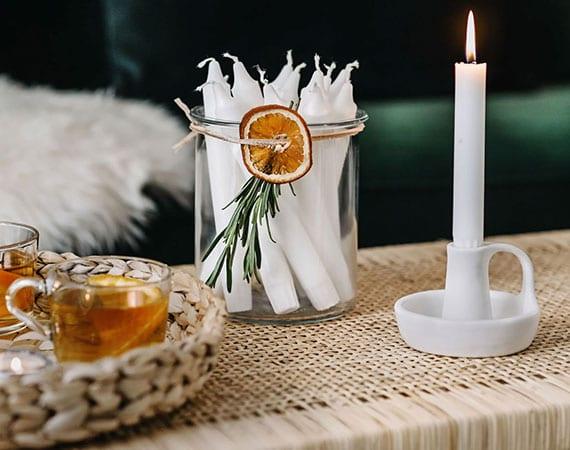 festliche tischdeko zu weihnachten mit weißenkerzen im glas, weidenschale und ikea kerzenhalter weiß