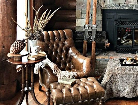 gemütliche atmosphäre dem wohnzimmer im winter verleihen durch rustikale winterdeko mit naturmaterialien, büchern und einer pelzdecke am ledersessel vor kamin aus naturstein