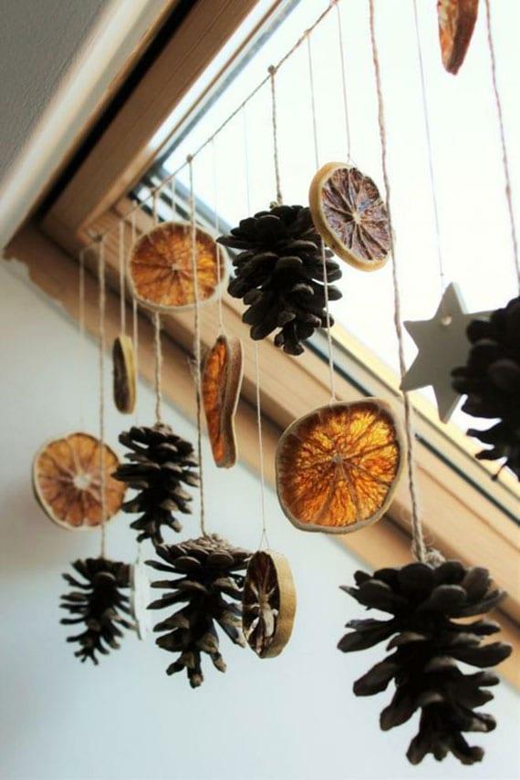 kreative fensterdeko idee zu weihnachten mit zapfen und orangenscheiben