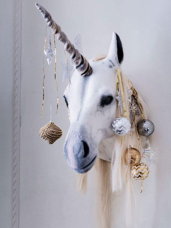 moderne wanddeko idee zu weihnachten mit einhorn-kopf und christbaumkugeln mit ornamenten in gold und silber