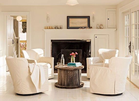 schöne winterliche einrichtungsidee für gemütliches wohnzimmer in weiß mit rundem DIY Vintage Couchtisch aus Holzrolle und drehesesseln vor kamin mit DIY kaminsims in weiß