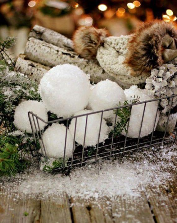 originelle diy winterdekoration mit dekorativen schneekugeln aus styropor und kunstschnee, tannengrün, birkenholz und zapfen in einem drahtkorb