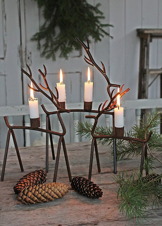 stilvolle tischdeko idee zu weihnachten mit zapfen, tannengrün und rentier-kerzenhalter aus metall
