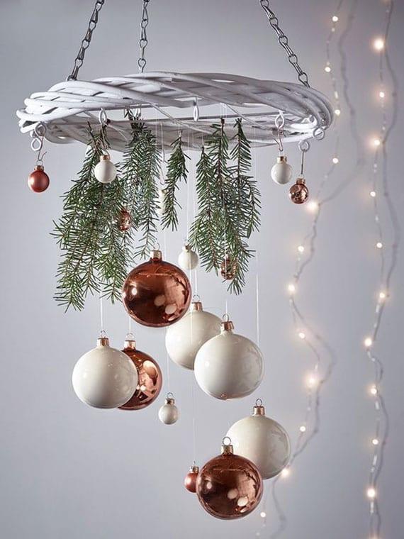 DIY weihnachtsmobile mit weißem weidenkranz, frischen tannenzweigen und großen christbaumkugeln in weiß und kupfer