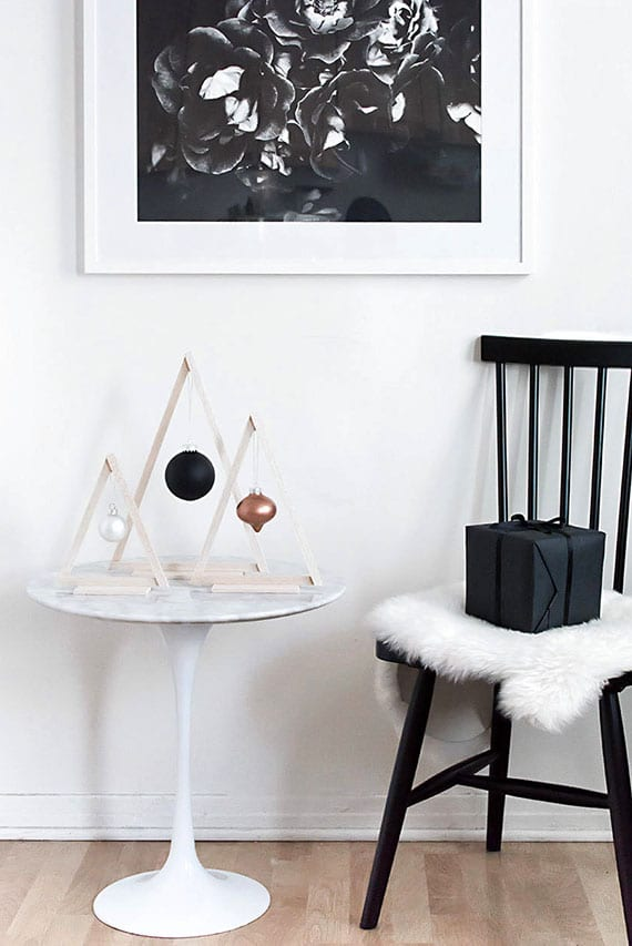 attraktive und moderne DIY weihnachtsdeko im nordischen stil mit christbaumkugel im dreieck-holzrahmen als tischdeko neben schwarzem holzstuhl mit weißem pelz und weihnachtsgeschenk