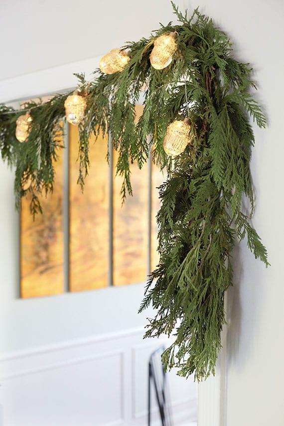 tolle einrichtungsideen zum wohlfühlen im winter durch fröhliche weihnachtsdeko für tür und kamin mit diy girlande aus immergrünzweigen und eichel-lichterkette