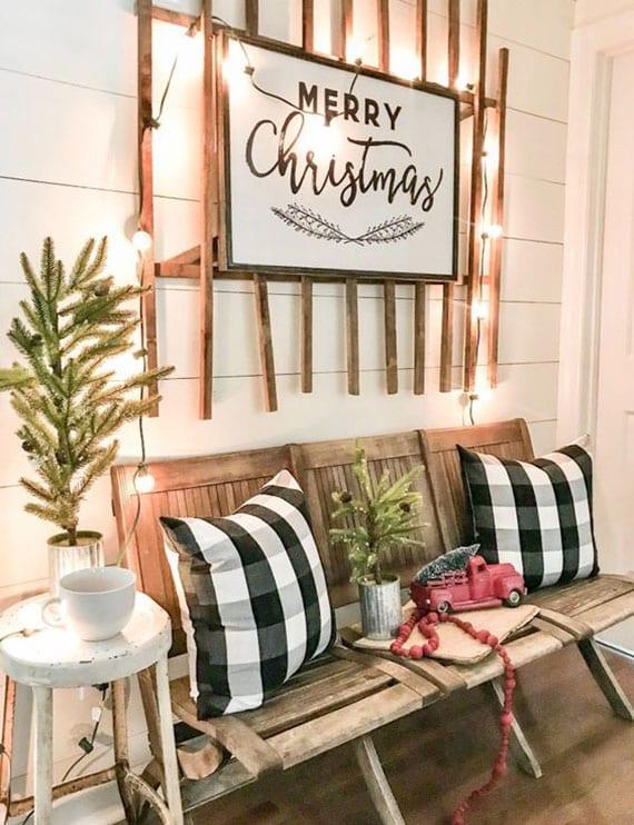 überdachte terrasse weihnachtlich einrichten mit holzbank, karrierten dekokissen, mini-tannenbäumen im topf, dia wanddeko aus holz, lichterkette und dekoaccessoires in rot