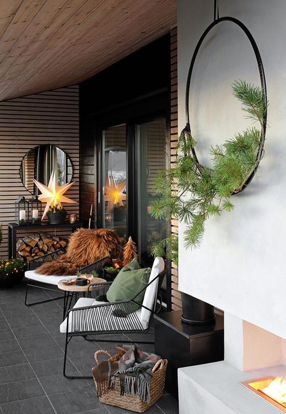 moderne gestaltungsidee für winterterrasse mit holzwandverkleidung, außenkamin, sideboard für deko und feuerholz, designer gartenmöbel mit polstern, rundem hocker-tisch und wanddeko mit diy tannengrün-kranz