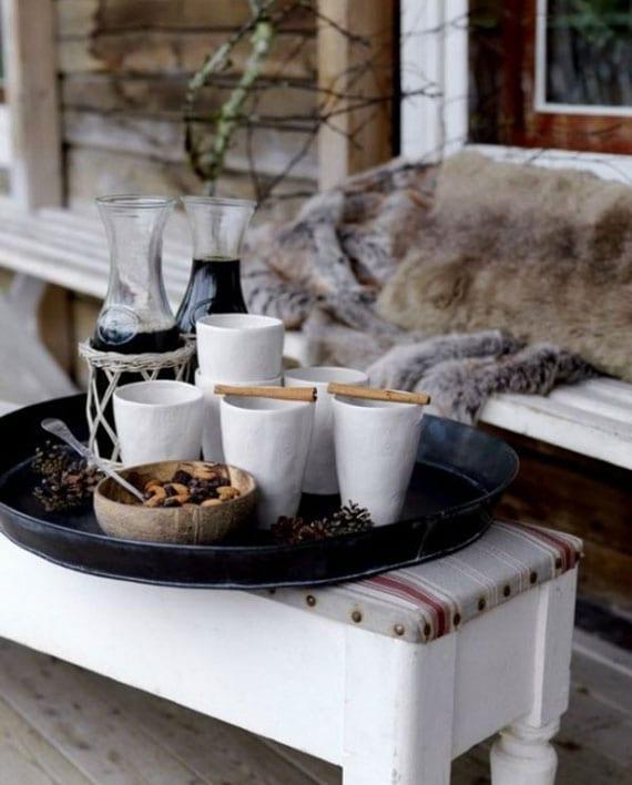 gemütliche winterliche terrassengestaltung mit weißen holzmöbeln, pelzdecken und kissen, serviertablett als beistelltisch für heiße getränke und naturdeko