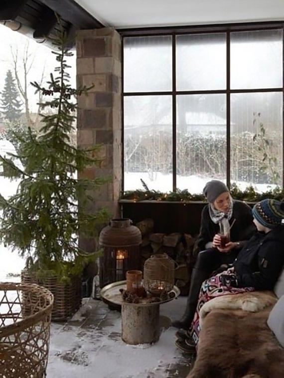 stimmungsvolle wintergestaltung der gartenterrasse mit tannenbaum im weidenkorb, sitzbank mit pelzüberwurf, diy kaffeetisch rund, laternen mit kerzen und feuerholz