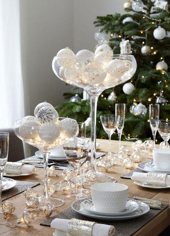 holzeestisch weihnachtlich eindecken mit grauem tisch-set, weißen servietten und geschirr, weißen christbaumkugeln und micro-leds im glas