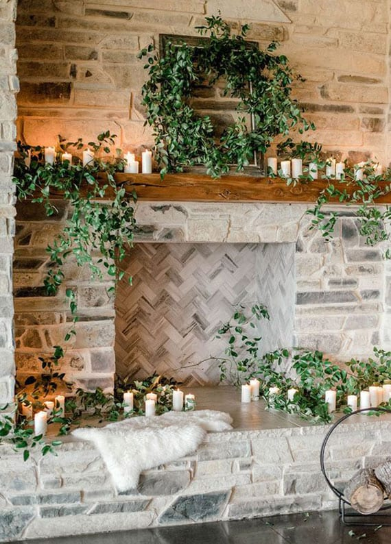 stilvolle Winter Deko Idee mit weißen Kerzen und frischem Grün für kamin aus naturstein mit holzbalken-regal