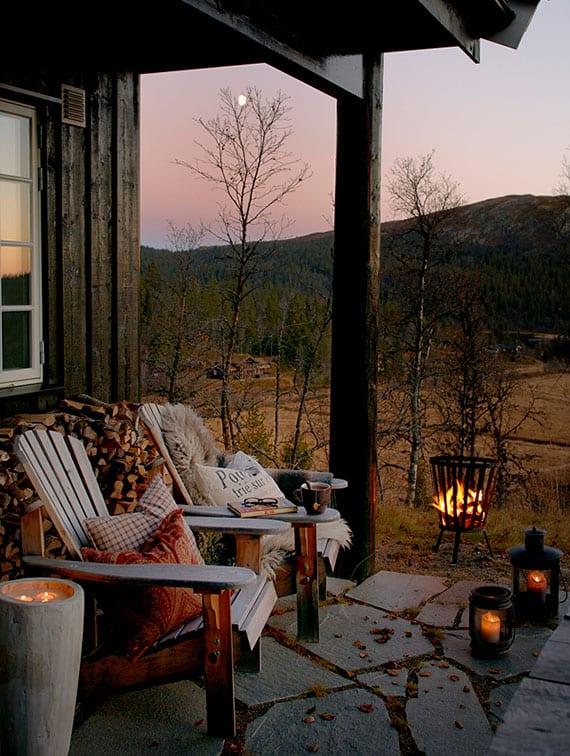 coole veranda ideen für gemütliche sitzecke im winter mit holzsesseln, kuscheligen kissen und decken, kerzenlicht aus laternen und mini feuerstelle