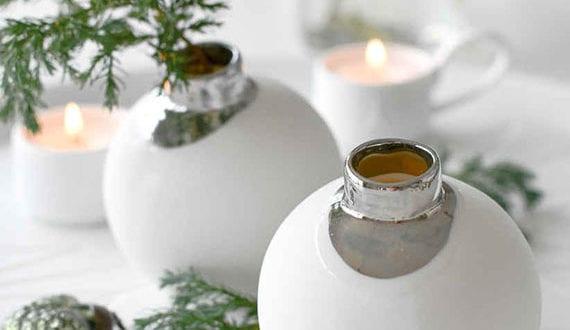 attraktive-deko-mit-weihnachtskugeln-als-weiße-mini-vasen-für-tannengrün