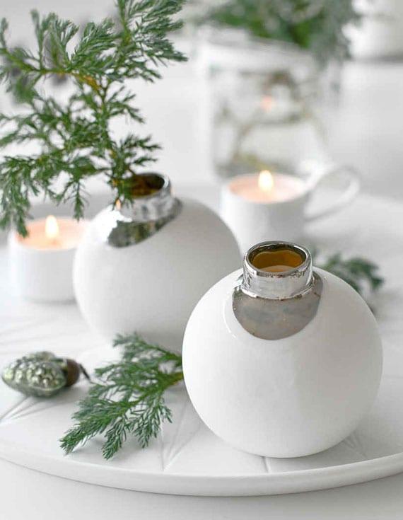 originelle weihnachtsdeko in weiß mit Weihnachtskugel-Vasen aus porzellan in runder schale weiß mit teelichter und tannengrünzweigen