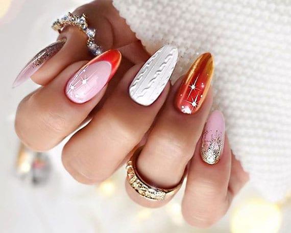 moderne wintermaniküre in weiß, rosa und orange mit gltzereffekt als tolle idee für schöne silvesternägel