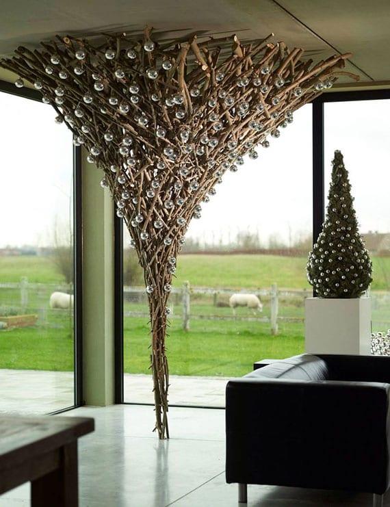 originelle deko idee zu weihnachten mit skulptur aus zweigen und silberfarbigen christbaumkugeln