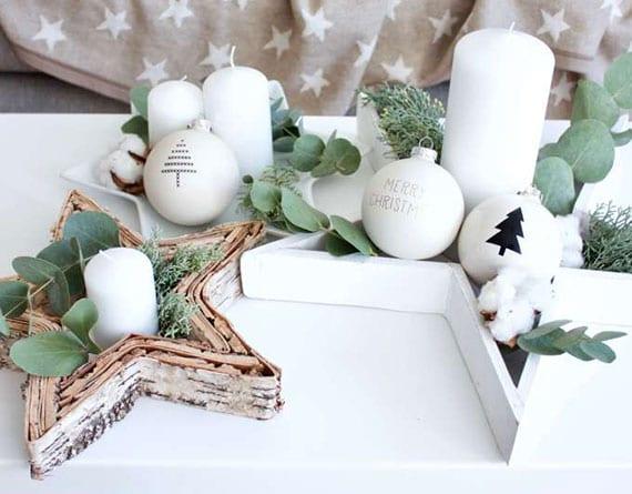 stilvolle adventskranz-tischdeko mit stern-schalen dekoriert mit tannengrün,eukalyptus,weißen kerzen und christbaumkugeln mit schwarzen ornamenten