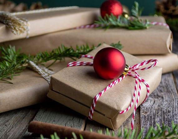 schöne verpackungsidee für weihnachtsgeschenke mit braunpapier, bäckergarn in rot und weiß und kleiner christbaumkugel rot