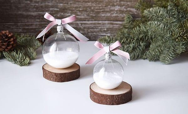 romantische und magische weihnachtsdeko mit glaskugeln und kunstschnee auf kleinen holzscheiben