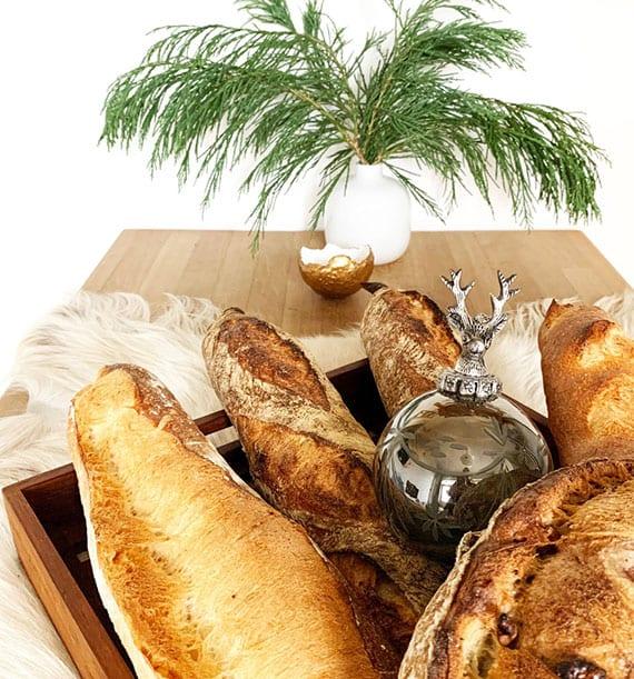 rustikale tischdeko zu weihnachten mit frischem Tannengrün in weißer vase, weiße pelzdecke und landbrot mit silberfarbiger christbaumkugel mit hirsch ornament in holztablett