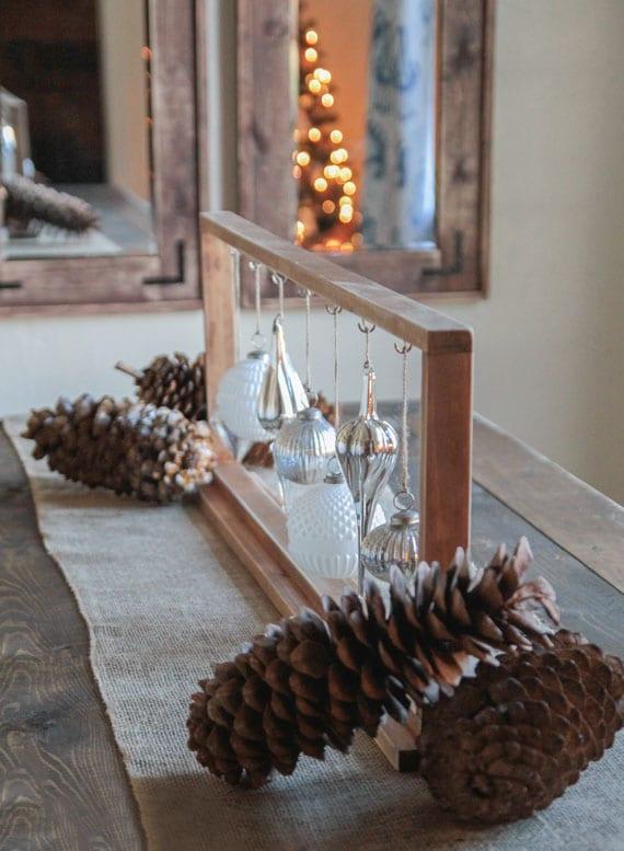 weiße und silberfarbige christbaumkugeln im holzrahmen als rustikale weihnachtsdeko selber machen und auf leinentischläufer mit naturmaterialien arrangieren