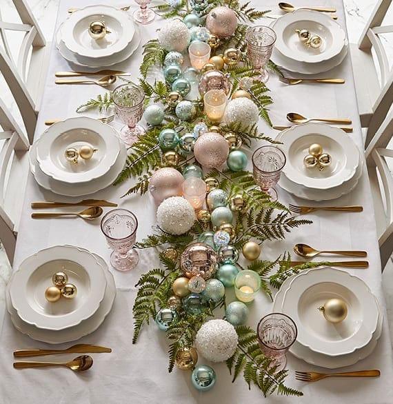 tisch zu weihnachten festlich und elegant decken mit goldbesteck, goldfarbigen christbaumkugeln als platzteller deko und unterschiedlich großen kugeln in pastellfarben